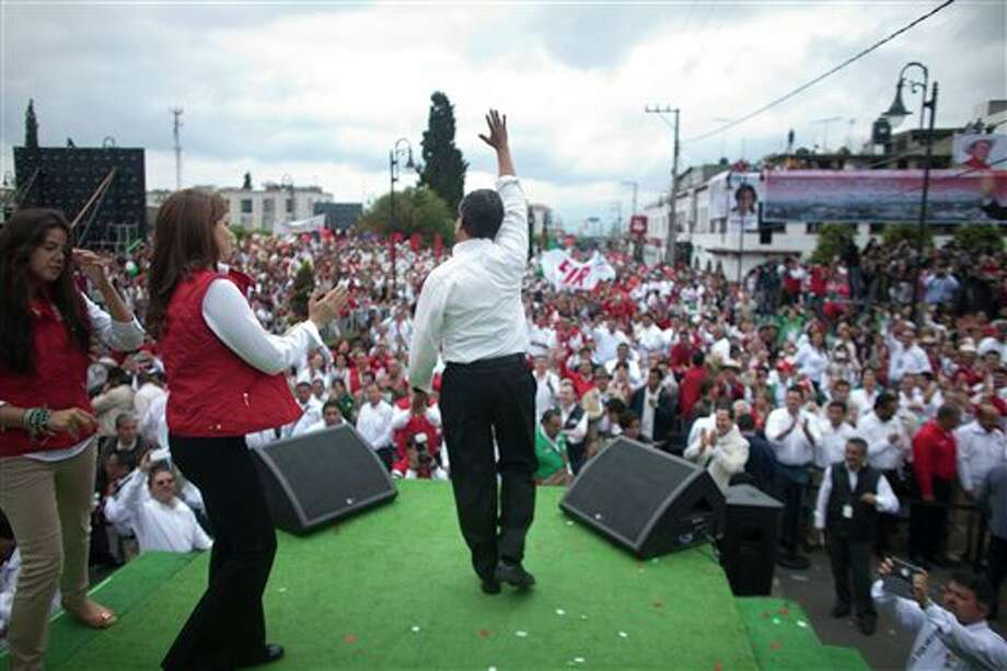 Presidential candidate Enrique Pena Nieto, of the Institutional Revolutionary Party, center, waves to supporters during a campaign rally in Atlacomulco, Mexico, Sunday, June 17, 2012. Mexico will hold presidential elections on July 1. (AP Photo/Alexandre Meneghini) (AP)