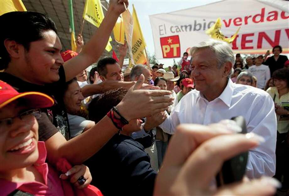 Andres Manuel Lopez Obrador, presidential candidate for the Democratic Revolution Party, PRD, right, greets supporters at a campaign rally in Cuautitlan Izcalli, Mexico,  Wednesday, June 6, 2012. Mexico will hold presidential elections on July 1. (AP Photo/Eduardo Verdugo) (AP)
