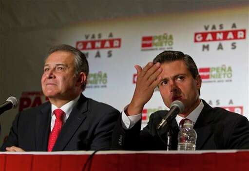 Presidential candidate Enrique Pena Nieto, right, of the Institutional Revolutionary Party and Colombian retired Gen. Oscar Naranjo attend a press conference in Mexico City, Thursday, June 14, 2012. Pena Nieto announced Thursday night that he will appoint Naranjo, who helped bring down late Colombia's drug kingpin Pablo Escobar, as an adviser, calling Colombia an example of success in drug war strategy. (AP Photo/Christian Palma) Photo: Associated Press