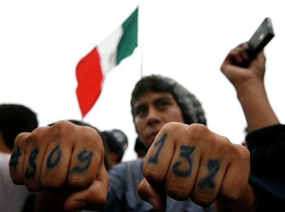 """A youth shows his fingers painted with the words """"#YoSoy132,"""" or """"I am 132"""" at a music fest in support of the student movement in Mexico City's Zocalo plaza, Saturday June 16, 2012.  #YoSoy132 is the name of a university movement that rejects the possible return of the old ruling Institutional Revolutionary Party (PRI) ahead of Mexico's July 1 presidential election. (AP Photo/Marco Ugarte) Photo: Associated Press"""
