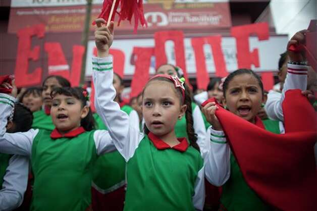 Children wearing clothes with the colors of the Institutional Revolutionary Party wave prior to the arrival of its presidential candidate Enrique Pena Nieto during a campaign rally in Atlacomulco, Mexico, Sunday, June 17, 2012. Mexico will hold presidential elections on July 1. (AP Photo/Alexandre Meneghini) Photo: Associated Press