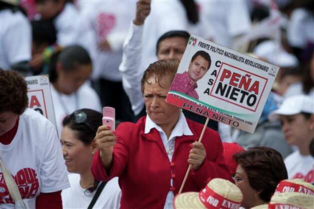 A supporter of presidential candidate Enrique Pena Nieto, of the Institutional Revolutionary Party, takes a picture with a mobile phone prior to his arrival for a campaign rally in Atlacomulco, Mexico, Sunday, June 17, 2012. Mexico will hold presidential elections on July 1. (AP Photo/Alexandre Meneghini) Photo: Associated Press