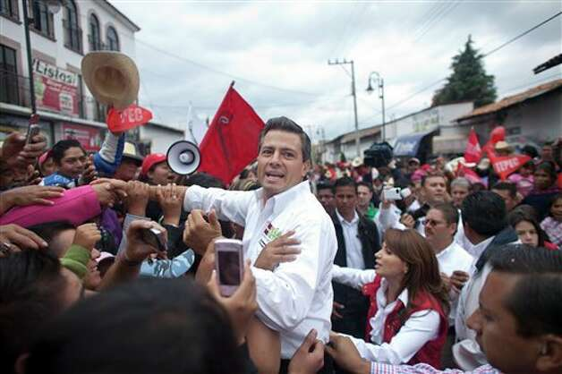 Presidential candidate Enrique Pena Nieto, of the Institutional Revolutionary Party, center, greets supporters during a campaign rally in Atlacomulco, Mexico, Sunday, June 17, 2012. Mexico will hold presidential elections on July 1. (AP Photo/Alexandre Meneghini) Photo: Associated Press