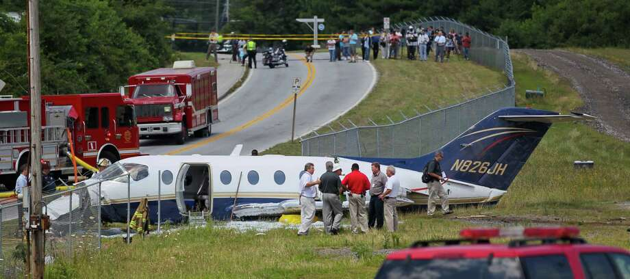 Officials inspect a downed aircraft Monday, June 18, 2012, near Atlanta. Authorities say all four people aboard a small jet were hurt when the aircraft ran off a runway in the Atlanta area. Federal Aviation Administration spokeswoman Kathleen Bergen says four people were on board the Hawker Beechcraft 40 that crashed through a fence after leaving the runway at DeKalb-Peachtree Airport around 10 a.m. Monday. (AP Photo/Atlanta Journal-Constitution, John Spink) Photo: John Spink, Associated Press / ©2012 Atlanta Journal Constitution