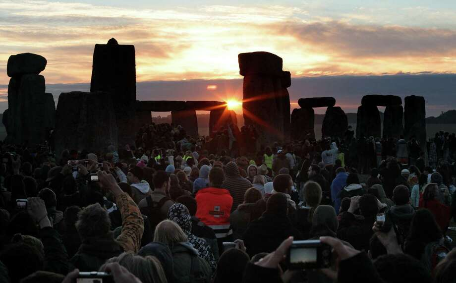 Revelers watch the sun rise over Stonehenge on Salisbury Plain, England, on the summer solstice. Photo: Matt Cardy, Getty Images / Getty Images Europe