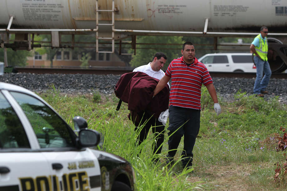 "Workers remove what they described as ""body parts"" from the Union Pacific railroad tracks near Kirk Place and 21st Street after a man was hit by a freight train Monday. Photo: San Antonio Express-News"