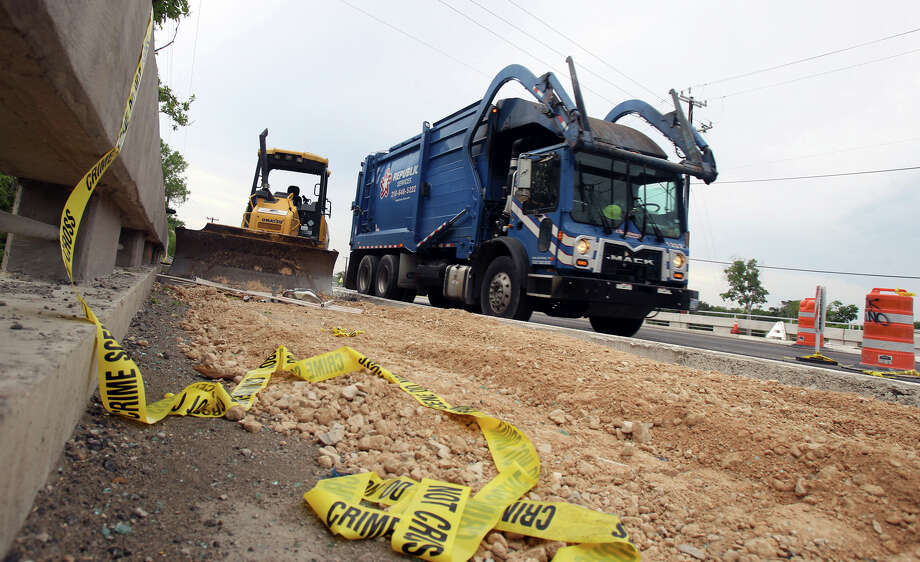 A garbage truck passes by construction equipment and crime scene tape where a woman and her four children died in an accident. Photo: John Davenport, San Antonio Express-News / John Davenport/San Antonio Express-News