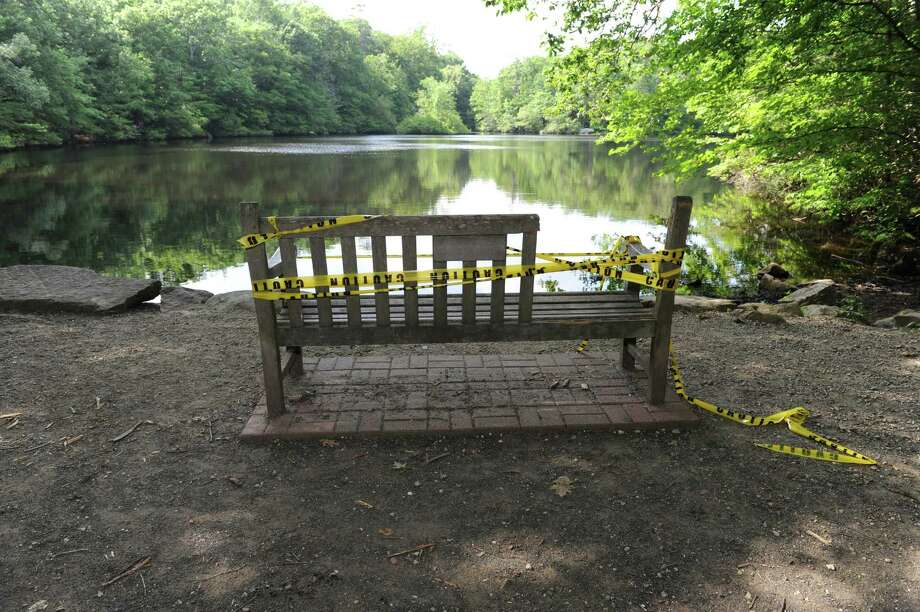 Police are investigating a possible vandalism of a memorial bench dedicated to 9/11 victim Joseph Lenihan in Pomerance Park on Cos Cob Pond. The bench, shown Monday, June 18, 2012, is missing a portion of its backing. Photo: Helen Neafsey / Greenwich Time