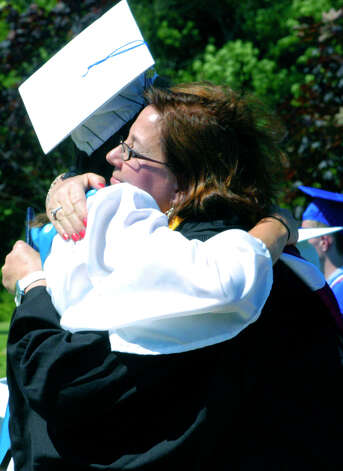 Class of 2012 member Colleen Koslosky receives her diploma, and a hug, from her mother, class advisor Cindy Koslosky, during the Shepaug Valley High School graduation ceremony, June 16, 2012, in Washington. Photo: Norm Cummings