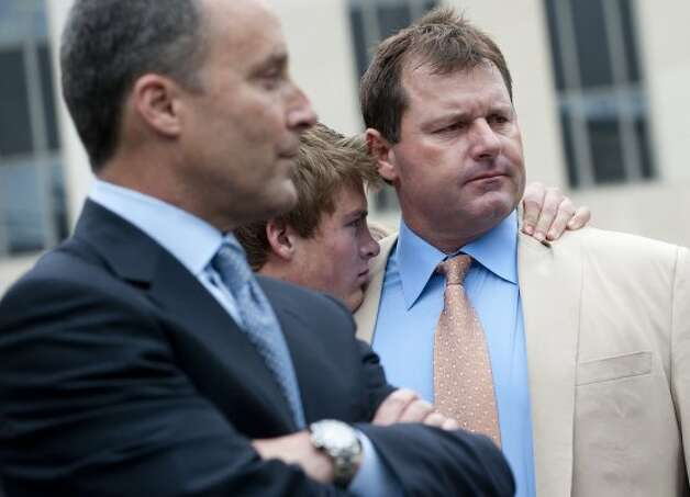 Roger Clemens, right, waits to speak to the media alongside a member of his family, center, and attorney Michael Attanasio. (SAUL LOEB / AFP/Getty Images)