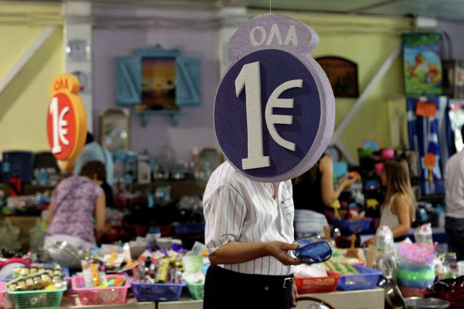 """Customers browsing discounted goods for sale at a """"one euro store""""  in Athens on Monday. Europe looked on with wary relief Monday following election of Greek conservative leader Antonis Samaras. Photo: Petros Giannakouris / AP"""