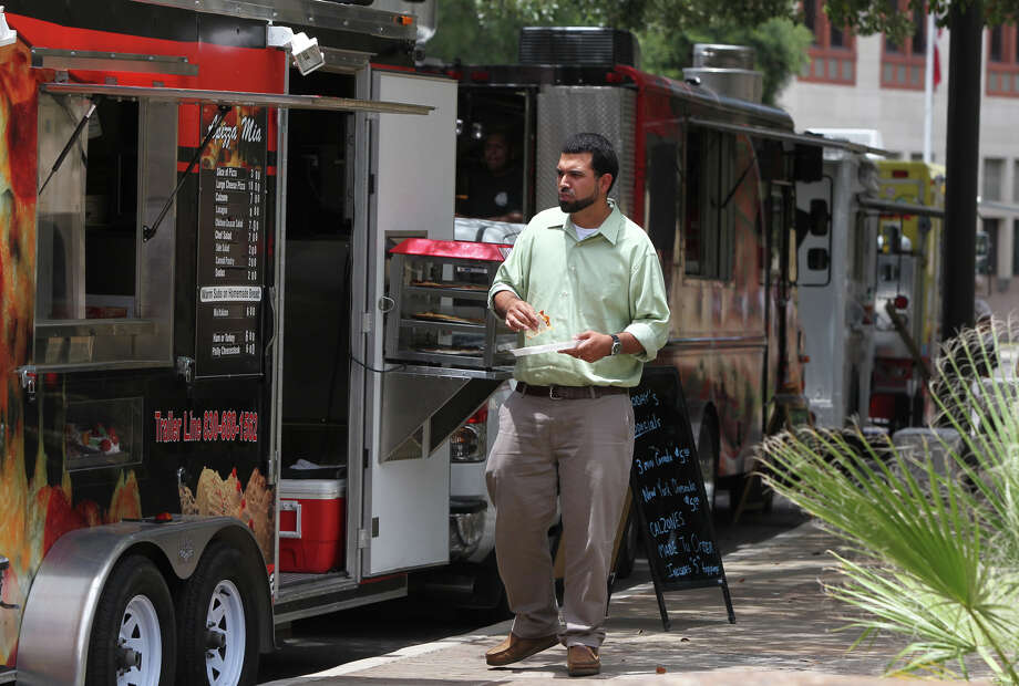 Ron Zepeda enjoys some Korean style barbecue from the Takoriya food truck at Main Plaza during the luch hour Monday June 18, 2012. There were four food trucks parked at Main Plaza Monday. Photo: San Antonio Express-News