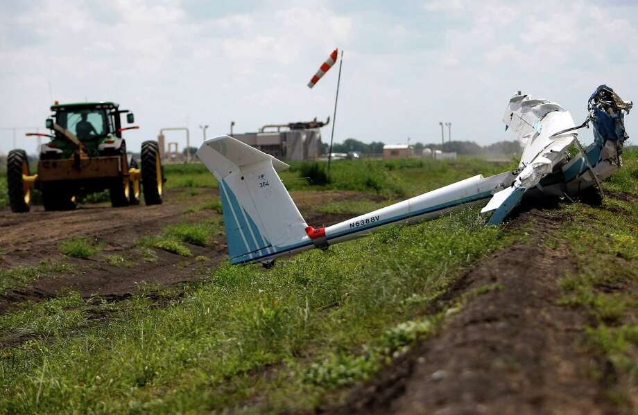 A landowner with a tractor helped first responders and National Transportation Safety Board investigators in removing the glider. Photo: Johnny Hanson / © 2012  Houston Chronicle