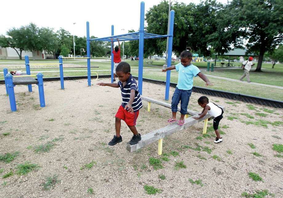 Armarion Bailey, 4 left, 6-year-old Surora McPherson and 3-year-old Roscoe Burrows play at Emancipation Park on Monday. ( James Nielsen / Chronicle ) Photo: James Nielsen / © Houston Chronicle 2012
