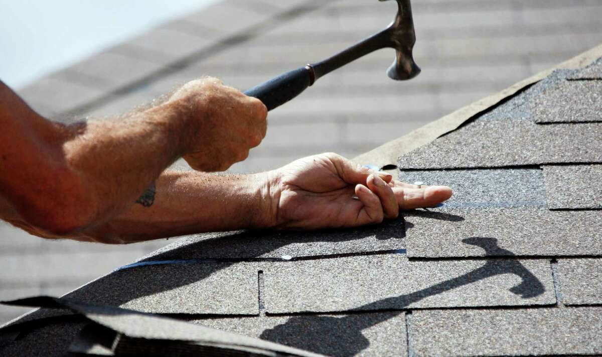 In this 2012 photo, Troy Drake hammers a shingle onto a new roof in Mississippi. (AP Photo/Rogelio V. Solis)