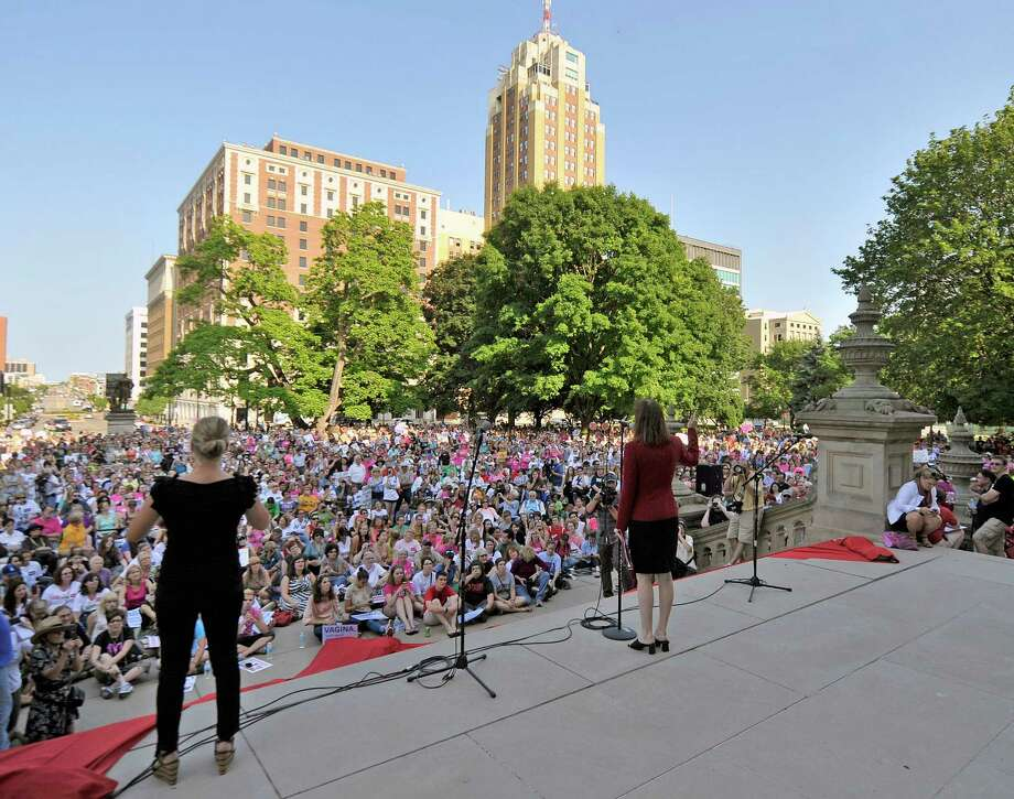 "Rep Lisa Brown, D-West Bloomfield, center, addresses supporters who gather for her performance of ""The Vagina Monologues""  with 10 other lawmakers and several actresses on the Michigan Statehouse steps, Monday, June 18, 2012, in Lansing, Mich. Brown, who says she was barred from speaking in the Michigan House because Republicans objected to her saying ""vagina"" during debate over anti-abortion legislation, performed ""The Vagina Monologues"" with a hand from the author Eve Ensler. (AP Photo/Detroit News, Dale G. Young) Photo: Dale G. Young / Detroit News"