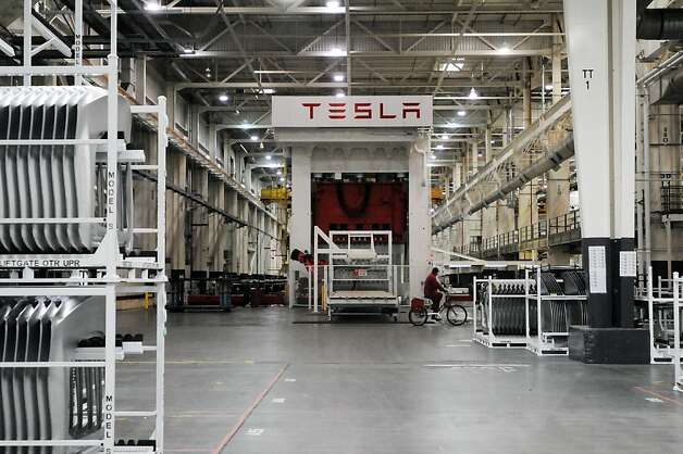 A Tesla sign decorates inside the factory in Fremont, Calif., Wednesday, June 13, 2012. On June 22, Tesla Motors will begin delivering its all-electric Model S luxury sedan. It is only the second car ever produced by Tesla, and first to be built at Tesla's own factory. Photo: Erik Verduzco, Special To The Chronicle