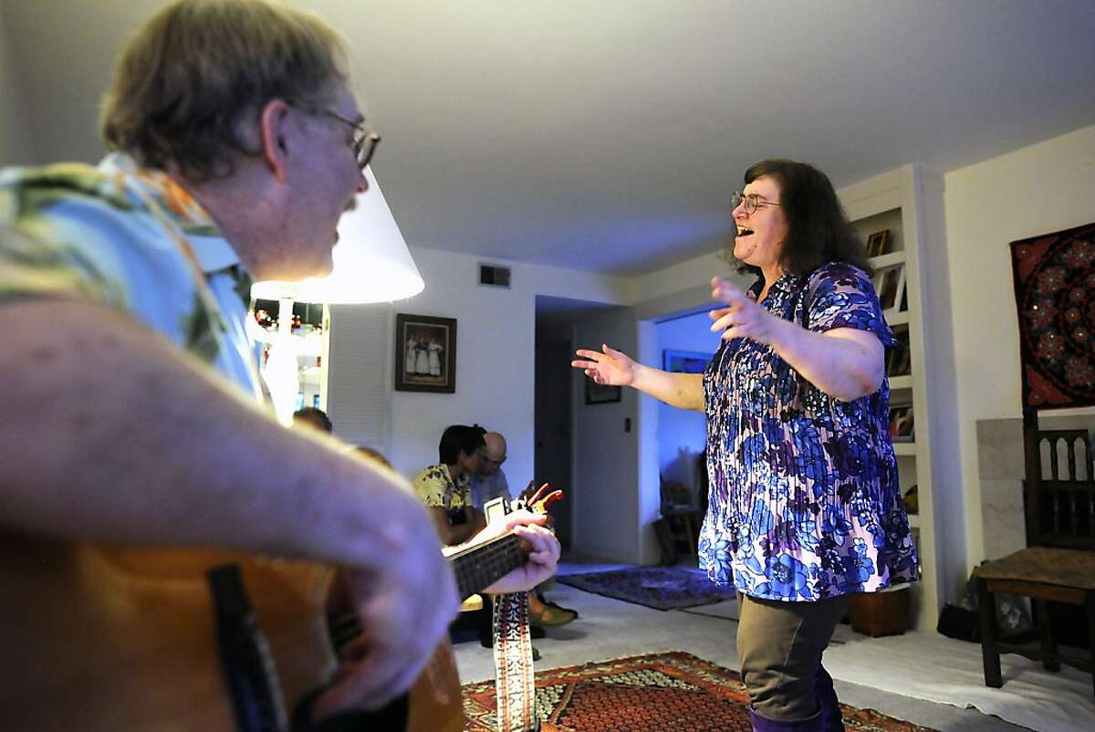 Marlene McCall(R) sings as Doug Norman plays guitar during a birthday party for Susan Sherrell at her home in Oakland CA Saturday June 16th, 2012