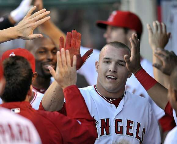 Los Angeles Angels' Mike Trout is greeted inside the dugout after scoring on a sacrifice hit by Los Angeles Angels Albert Pujols in the first inning, Monday, June 18, 2012, at Angel Stadium in Anaheim, California. (Rose Palmisano/Orange County Register/MCT) Photo: Rose Palmisano, McClatchy-Tribune News Service