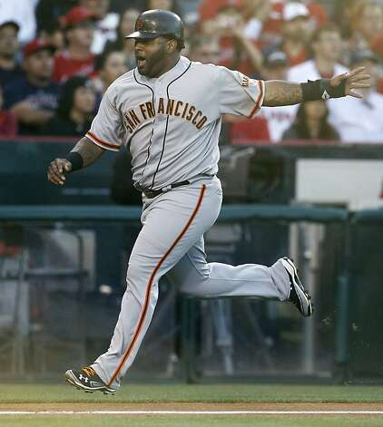 San Francisco Giants' Pablo Sandoval reacts as he scores on a two run-triple by Brandon Crawford against the Los Angeles Angels during the second inning of a baseball game in Anaheim, Calif., Monday, June 18, 2012. (AP Photo/Chris Carlson) Photo: Chris Carlson, Associated Press