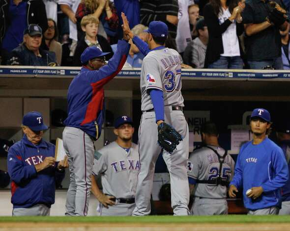 Texas Rangers relief pitcher Mike Adams gets a high five from Texas Rangers manager Ron Washington after pitching out of trouble against the San Diego Padres during the eighth inning of a one run baseball game Monday, June 18, 2012 in San Diego. Photo: Lenny Ignelzi, Associated Press