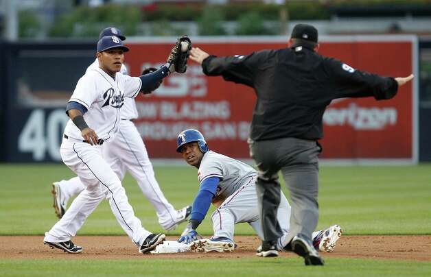San Diego Padres shortstop Everth Cabrera, left, holds up the ball as he and Texas Rangers baserunner Elvis Andrus look to umpire Brian Knight, right, who gives the safe call on a stolen base during the first inning of an interleague baseball game, Monday, June 18, 2012, in San Diego. Photo: Lenny Ignelzi, Associated Press