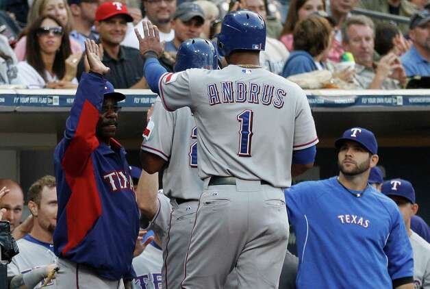 Texas Rangers' Elvis Andrus follows Adrian Beltre to the dugout while getting a high-five from manager Ron Washington, left, after the paired scored on a David Murphy single in the first inning of a baseball game, Monday, June 18, 2012, in San Diego. Photo: Lenny Ignelzi, Associated Press