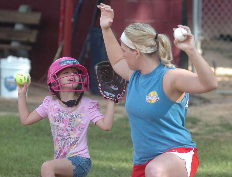 Meagan Weldon teaches a young camper some of the finer skills of softball during Monday's softball camp. Photo: Jimmy Galvan
