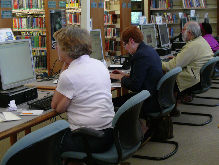 The bank of computers at the Fairfield Woods Branch Library was fully in use Monday afternoon. Both branches of the Fairfield Public Library will operate on reduced hours starting July 1 to accommodate budget cuts. Photo: Genevieve Reilly / Fairfield Citizen