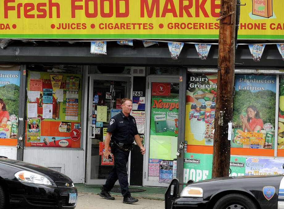 Police officers stand outside Hope Fresh Food Market on Tuesday, June 19, 2012, after a reported armed robbery in the Hope Street store. Photo: Lindsay Niegelberg / Stamford Advocate