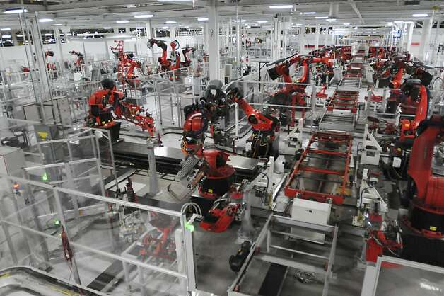 Machines are used to assemble parts for Tesla's Model S sedan at the factory in Fremont. Delivery begins Friday. Photo: Erik Verduzco, Special To The Chronicle