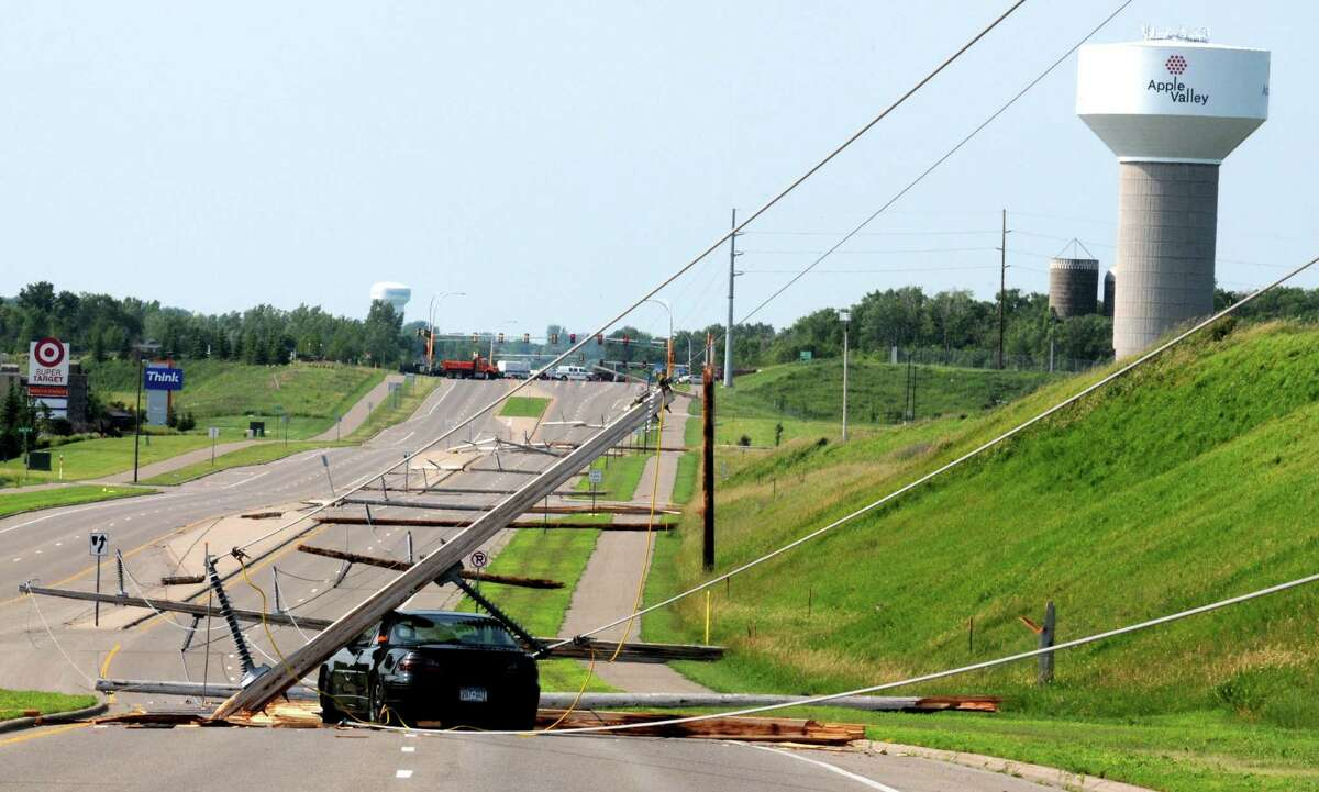A crushed car and a line of downed power lines looking on Pilot Knob Road and County Road 42 in Apple Valley, Minn., after high winds caused damage and power outages throughout the Twin Cities metro area, Tuesday morning. (AP Photo/St. Paul Pioneer Press, John Doman)