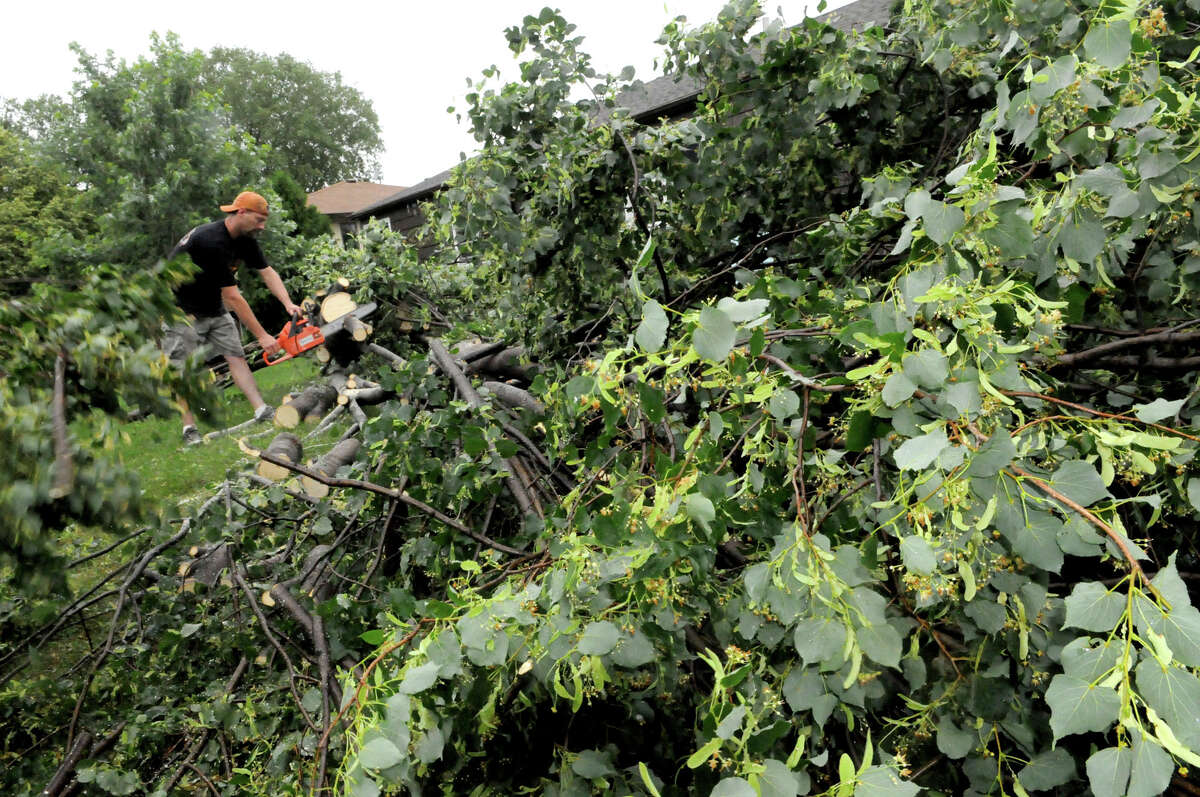 James Horsch works clears away the huge shade tree that fell in his front yard at 75 W. Logan Ave. in West St. Paul after high winds caused damage and power outages throughout the Twin Cities metro area, Tuesday morning. (AP Photo/St. Paul Pioneer Press, John Doman)