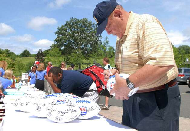 Dick Swatland signs footballs at the NFL Alumni CT Chapter  6th Annual Charity Golf Classic at Country Club of Darien in Darien, Conn. on Monday June 18, 2012. Photo: Dru Nadler / Stamford Advocate Freelance