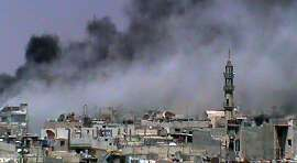 "A handout image released by the Syrian opposition's Shaam News Network shows smoke rising from a building in the Khalidiyah neighbourhood of the restive city of Homs on June 8, 2012. Syrian government forces pounded a neighbourhood of the eastern city of Deir Ezzor with mortar fire on June 11, killing 10 civilians including a young girl, a monitoring group said. AFP PHOTO/HO --- RESTRICTED TO EDITORIAL USE - MANDATORY CREDIT ""AFP PHOTO / HO / SHAAM NEWS NETWORK"" - NO MARKETING NO ADVERTISING CAMPAIGNS - DISTRIBUTED AS A SERVICE TO CLIENTS - AFP IS USING PICTURES FROM ALTERNATIVE SOURCES AS IT WAS NOT AUTHORISED TO COVER THIS EVENT, THEREFORE IT IS NOT RESPONSIBLE FOR ANY DIGITAL ALTERATIONS TO THE PICTURE'S EDITORIAL CONTENT, DATE AND LOCATION WHICH CANNOT BE INDEPENDENTLY VERIFIED ----/AFP/GettyImages"