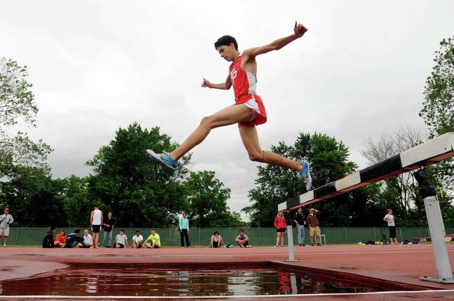 NEW BRITAIN 06/13/12 Fairfield Prep's Christian Alvarado leaps over the water on his way to winning the 3,000 meter steeplechase event at Willow Brook Park in New Britain.  CLOE POISSON|cpoisson@courant.com Photo: Cloe Poisson, Hartford Courant / \20120606\B582165287Z.1