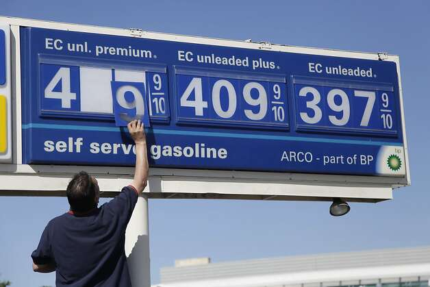 An Arco gas station worker lowers the prices on a sign at a Arco gas station in Palo Alto, Calif., Friday, June 15, 2012. Oil is climbing slightly ahead of a weekend election in Greece that could prove crucial to Europe's efforts to bolster its sagging economy. (AP Photo/Paul Sakuma) Photo: Paul Sakuma, Associated Press
