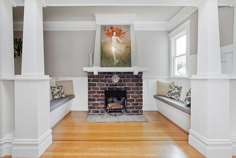 The home's foyer opens into the spacious, light-filled family room featuring, as its centerpiece, a wood-burning fireplace centered between custom built benches. Photo: OpenHomesPhotography.com