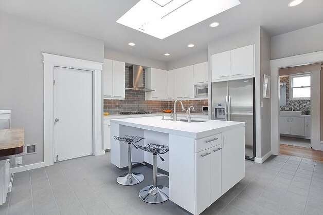 The home's modern kitchen has a large skylight and stainless steel appliances. Photo: OpenHomesPhotography.com