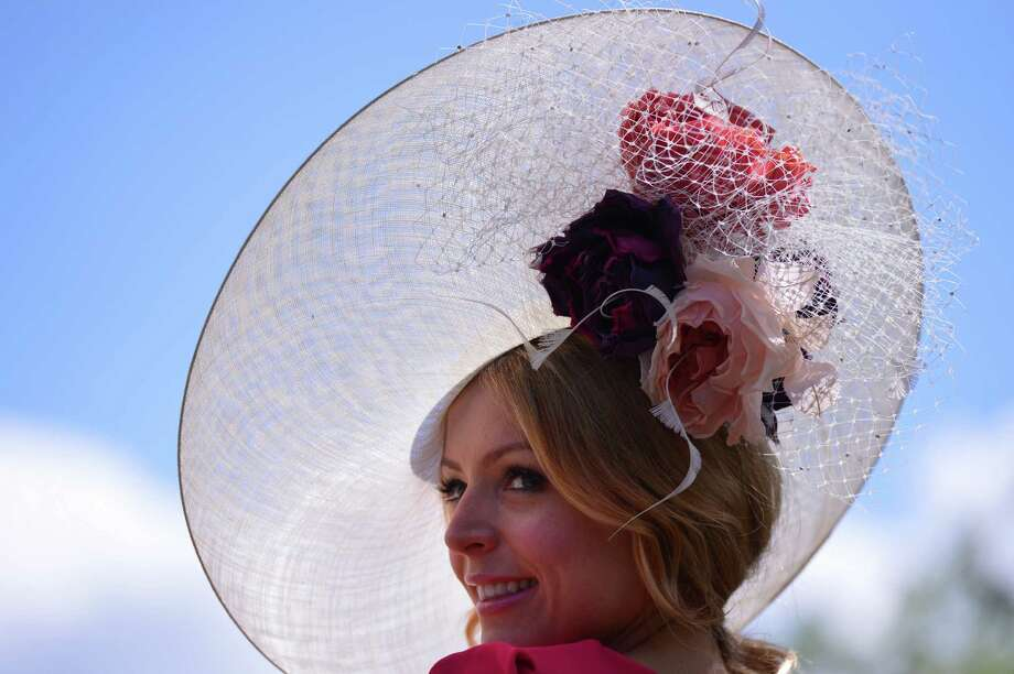 A race-goer wearing a flamboyant hat poses for the media at the annual Royal Ascot horse racing event near Windsor, Berkshire on June 19, 2012. The five-day meeting is one of the highlights of global horse racing and the pinnacle of the English social calendar. AFP PHOTO / CARL COURT        (Photo credit should read CARL COURT/AFP/GettyImages) Photo: CARL COURT, AFP/Getty Images / 2012 AFP