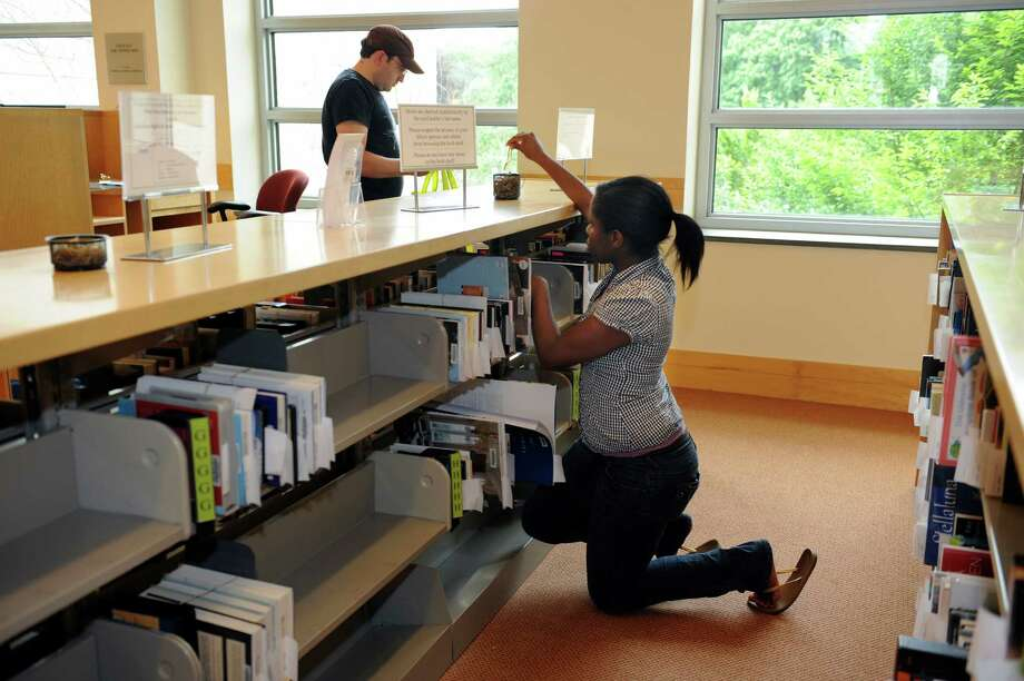 Librarian Kasandra Charles puts books in the new self-service pickup area at Greenwich Library in Greenwich Tuesday, June 19, 2012. The library released its new strategic plan, the culmination of an 18-month process which included a community-wide survey, focus groups, a trustee survey, a staff survey and retreat and work with a consultant. Photo: Helen Neafsey / Greenwich Time