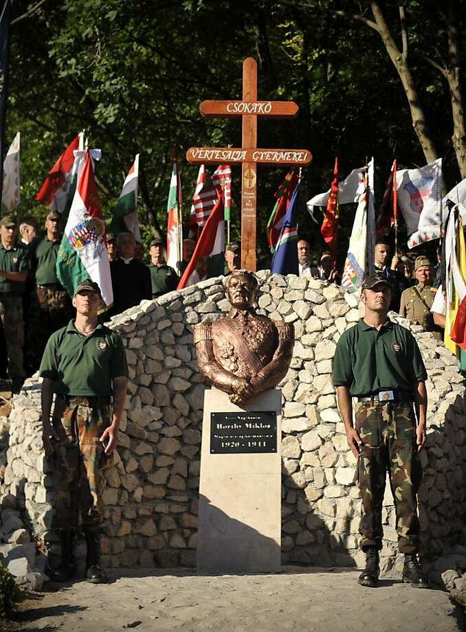 This photo taken June 16, 2012 shows members of the controversial far-right Hungarian Guard standing by the unveiled bust of Admiral Miklos Horthy, Hungary's  WWII ruler in Csokako, Hungary. Erecting a memorial for the controversial Horthy was welcomed by the Hungarian right wing, while the act was widely criticized by the country's liberal society. (AP Photo/Bela Szandelszky) Photo: Bela Szandelszky, Associated Press
