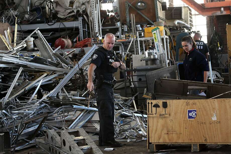 A police officer and pollution prevention specialist Claudia Pingatore (right) see metal taken from the Caltrans highway 4 corridor project (foreground middle left) as they investigated Christenson's recycling in Pittsburg, California, on Tuesday, June 19, 2012.  There were planned coordinated raids on metal recyclers this morning as part of a probe into metal theft. Photo: Liz Hafalia, The Chronicle