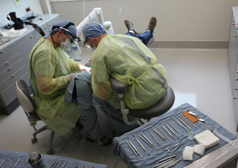 Periodontics resident Capt. John Teepe (left) and dental technician Airman  First Class Roger Golden work on  a patient  at the  Air Force Postgraduate Dental School at Joint Base San Antonio-Lackland. Photo: Jerry Lara, San Antonio Express-News / © 2012 San Antonio Express-News