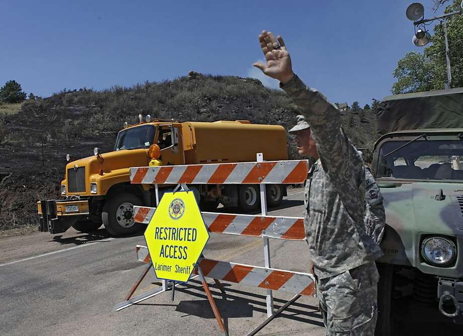Colorado Army National Guard Spc. Randall Orvis stops a uncoming vehicle so a water tanker can pass at a road block on the High Park wildfire   near Bellvue,  Colo., on Tuesday,  June 19, 2012. The National Guard has been assisting the Sheriff with road blocks. The wildfire has burned over 180 homes.  (AP Photo/Ed Andrieski) Photo: Ed Andrieski, Associated Press