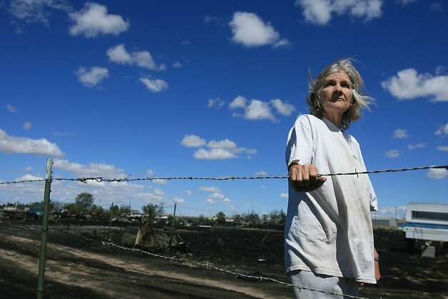 June Jeffery stands near her burned property  in Mountain Home, Idaho, Tuesday June 19, 2012. Jeffery lost 42 chickens when a fire burned through her property Monday night. The fire, which started Monday evening, has burned 150 acres, destroyed six residences and several outbuildings. (AP Photo/The Idaho Statesman, Chris Butler)  MANDATORY CREDIT Photo: Chris Butler, Associated Press