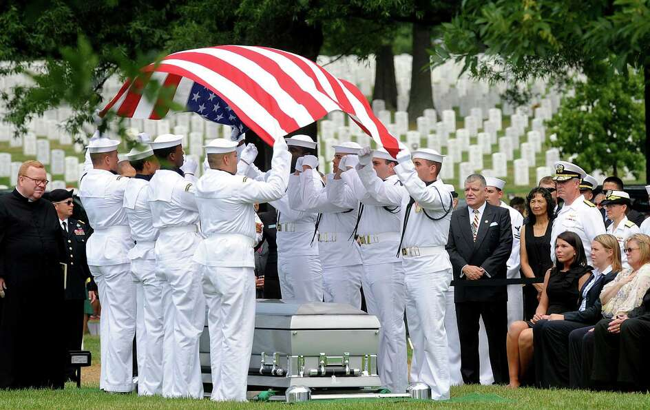 Honor guard team folds the American flag over the casket of U.S. Navy Petty Officer 2nd Class Sean E