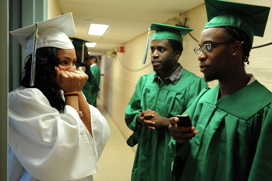 Eshae Johnson tries to contain her excitement as she waits with classmates Tevin McFadden and David Howard prior to the start of graduation exercises for the Bassick High School Class of 2012, held at the Klein Memorial Auditorium, in Bridgeport, Conn., June 19th, 2012. Photo: Ned Gerard / Connecticut Post