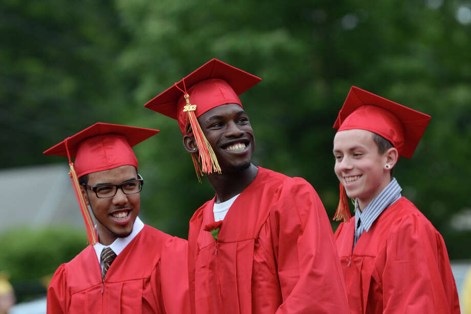 Jordan Reese Crumpton, center, flashes a smile to the crowd as he walks with fellow graduate Corey Ilidio Leite, left, during Stratford High School's 123rd Commencement at Penders Field in Stratford on Tuesday, June 19, 2012. Photo: Amy Mortensen / Connecticut Post Freelance