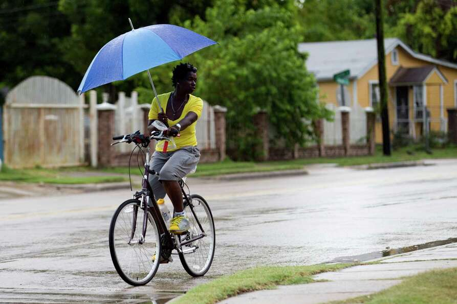Anita Hines uses an umbrella to protect herself from the rain as she rides her bicycle along Main ne